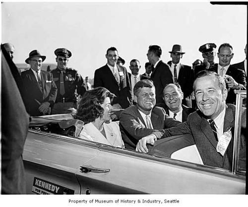 President John F. Kennedy and Others in Convertible, Seattle, 1961President Kennedy rode in a white convertible at the head of a parade of cars along Fourth Avenue as more than 50,000 people cheered his arrival in Seattle. Seated with the Chief Executive is Governor Albert D. Rosellini and Senator Henry M. Jackson.Photographer: Seattle Post-Intelligencer Staff PhotographerDate:1961Image Number:1986.5.31188.1To order a reproduction or to inquire about permissions contact photos@seattlehistory.org or phone us at 206-324-1126. Please refer to the Image Number and provide a brief description of the photograph.