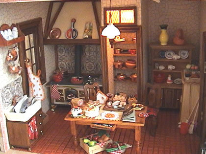 LA COCINA En la cocina quería plasmar el ambiente rústico de una casa de campo por eso realicé la campana y la despensa unidas. En el hueco que queda al otro lado de la despensa tengo unaparador rústicoprocedente de un fascículo (había pensado hacermelo, pero este queda bien de momento) para colocar la vajilla y accesorios de cocina. En la pared de al lado quiero poner lanevera Ladespensatiene luz independiente y no veo el momento de poder llenarla de viandas. Allí pondré también el microondas las cajas de verduras son imanes de la nevera. La campana está hecha con madera y luego pintada con pintura con arena para darle un aspecto rugoso. Unos listoncitos de madera aportan el detalle rústico. Losazulejosaunque no se ven muy bien han quedado muy bonitos pegando el dibujo escogido sobre un cartón luego lo recortas en cuadraditos y lo vuelves a pegar ligeramente separados. Por último le das una capa de barniz cerámico para que brille o brillo de uñas Lamesa de la cocinala he hecho con madera de balsa. Los detalles de fimo algunos son regalos de las amigas del grupo de miniaturas, otros como la tarta de nata están hechos por mi Elsuelode la cocina lo he hecho yo con barro de secado al aire.Vertrucos/ suelos La teja pintada al óleo es un regalo de Mila Elfregaderolo he hecho con pasta de modelar de secado al aire blanca y luego barnizándolo con el barniz de aspecto de porcelana. Los cajones se abren individualmente y cómo podéis ver ha quedado muy bien.