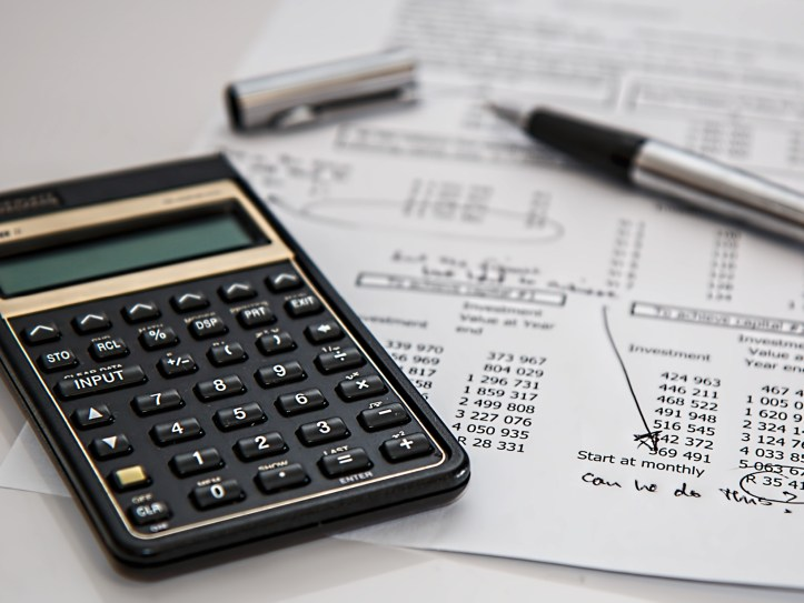 calculator and pen on table with spreadsheet