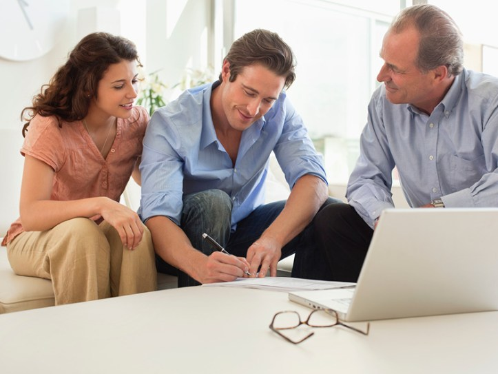 couple discussing purchase with man at table