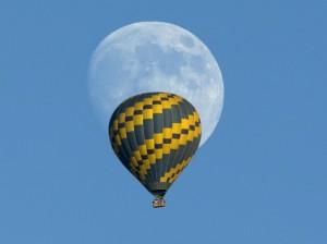 Hot air balloon floats past an almost full rising moon on a warm fall evening near Encinitas, California