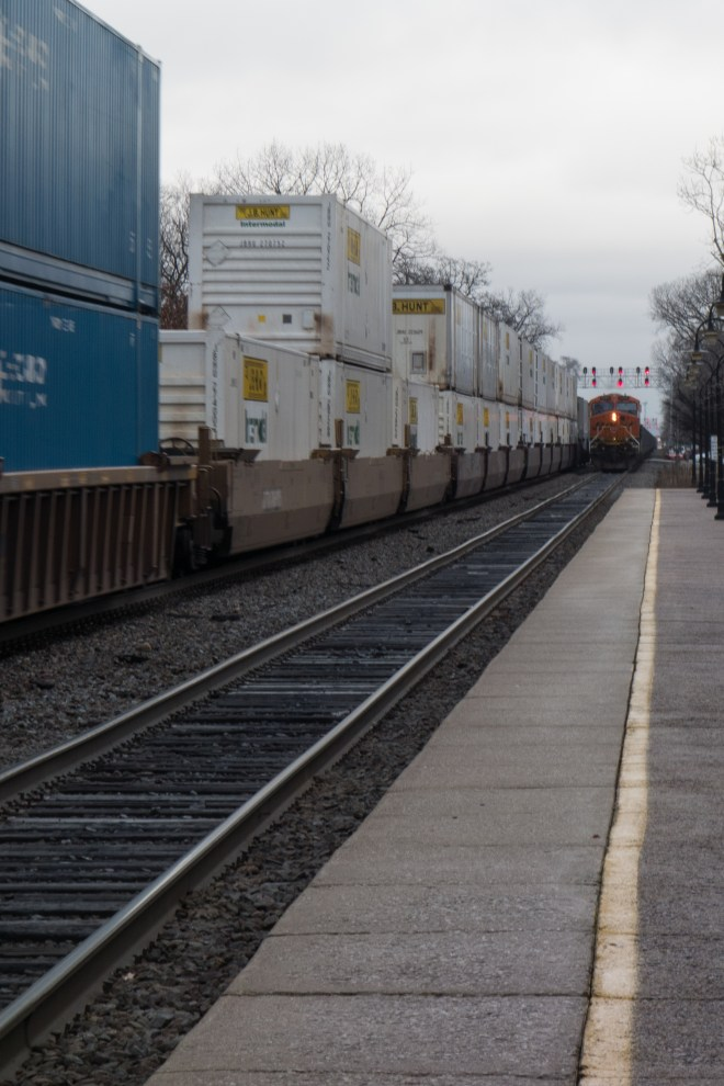 """A container """"Z"""" train heads west while a trailing unit pushes an empty coal train into Chicago."""