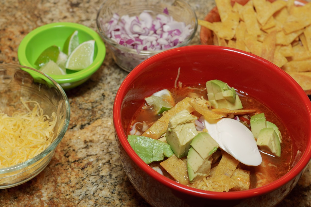 Dinner is served! Slow cooker chicken tortilla soup with all the fixings.