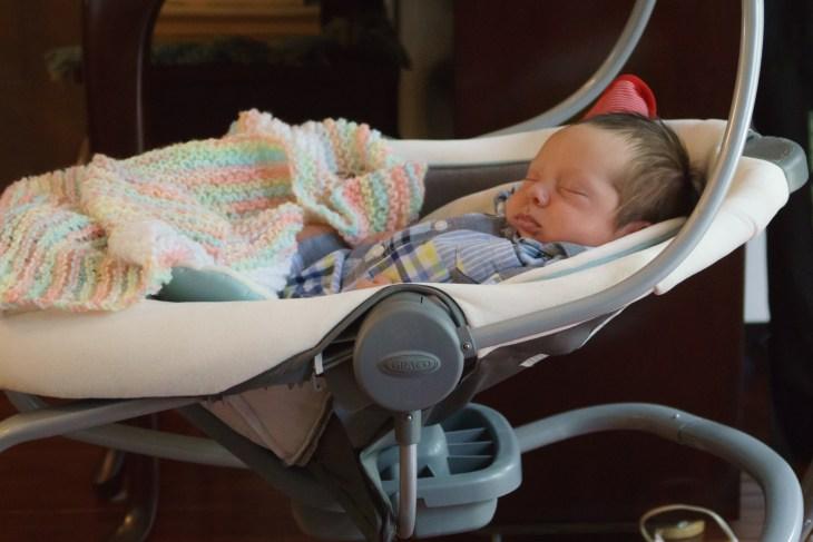 Little newborn C sleeping in his swing