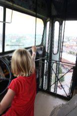 Vilja sitter i förarsätet på en skolbuss som hänger över taket på 11:e våningen