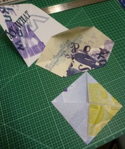 L to R: first fold along the diagonal, then points to center, ending up with another square
