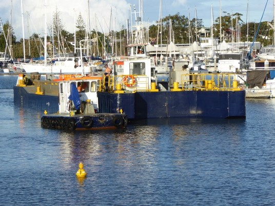 The little tender nudged the barge away from the dredger.