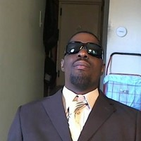 Dennis Sumlin headshot in a suit and tie with sunglasses