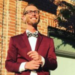 Cory Truax Stands against a brick wall while wearing a bow tie.