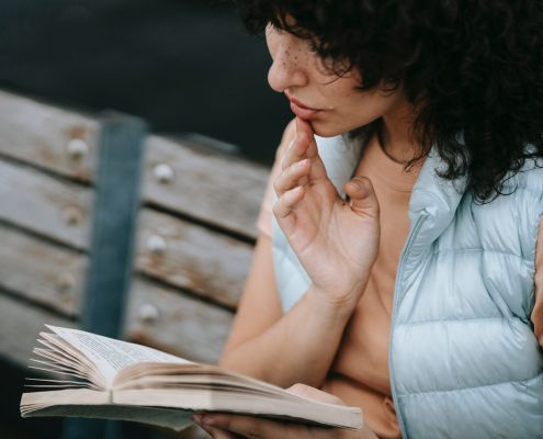 A woman reading a book, she looks very absorbed in it