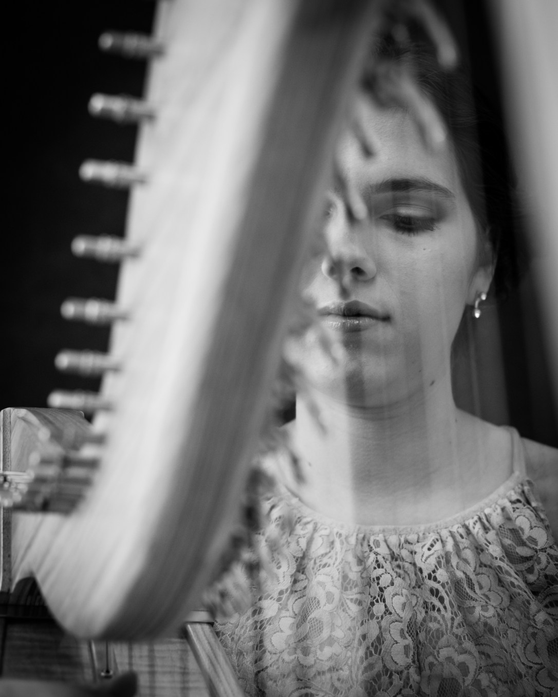 Close up of wedding harpist, through the strings