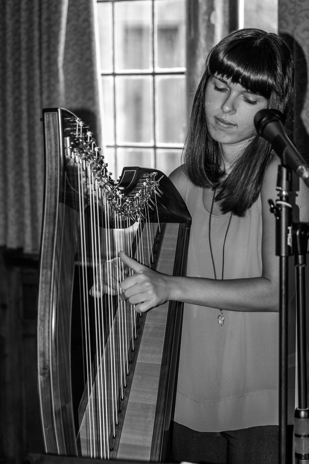 Female harpist with small 27 string Mark Norris Harp and Singing Microphone, black and white image