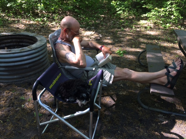 Joe Zellner and Izzy the dog chillin on a campsite.