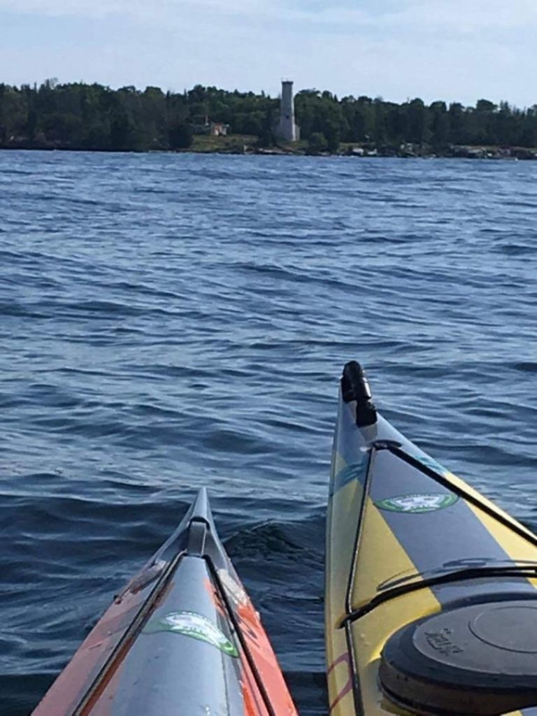 Poverty Island Lighthouse viewed from front of 2 kayaks.