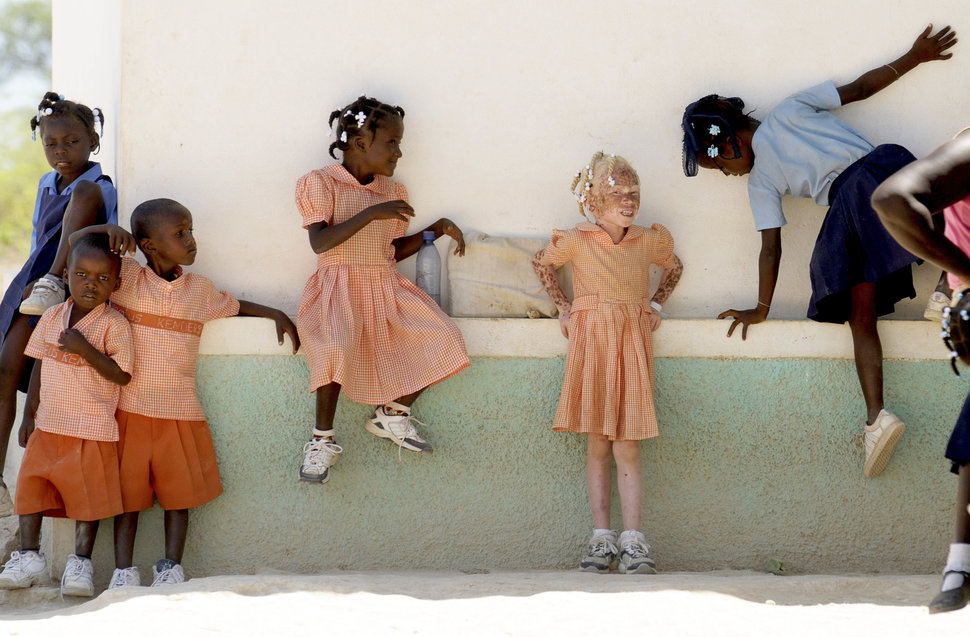 HAITI, Isla de la Laganave, School childrem in uniform playing, including an Albino girl.