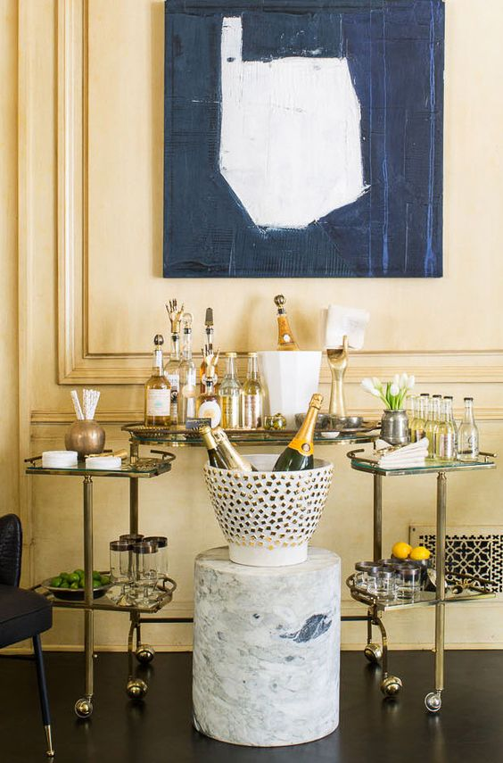 Brass bar cart with stone centerpiece and glass/gold elements to give a luxurious feel