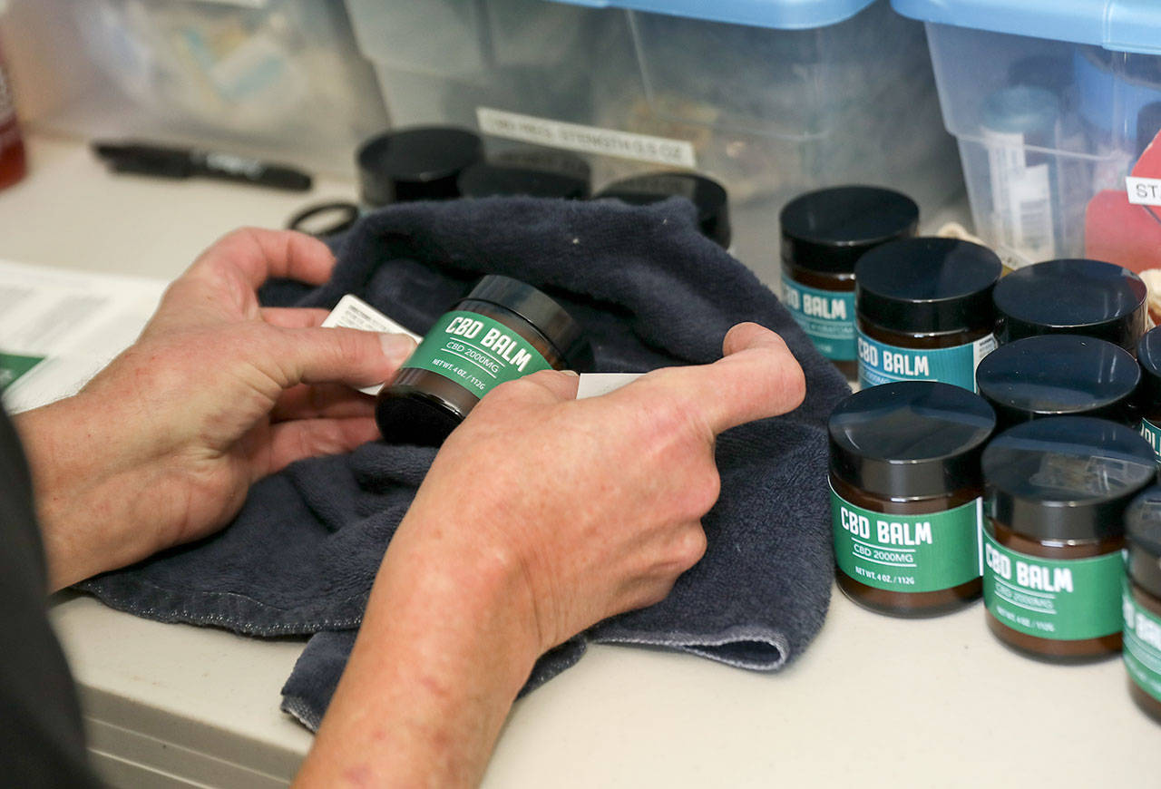 Ron Gordon puts the finishing touches on the CBD balm that he makes at the Snohomish Senior Center. (Lizz Giordano / The Herald)