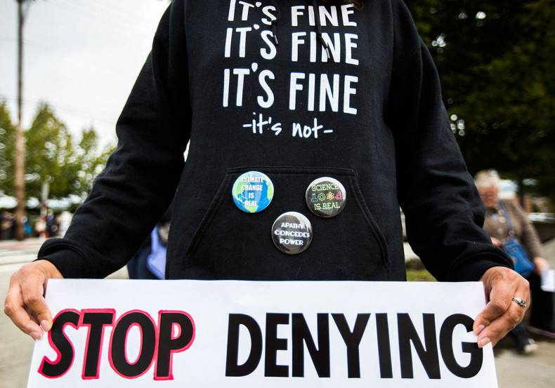 A protestor wears a sweatshirt and pins protesting climate change denial during the Global Climate Strike at the Snohomish County Campus Plaza on Sept. 20, 2019, in Everett. (Olivia Vanni / Herald file)