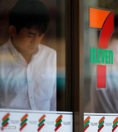 The Seven & I Holdings Co., right, and 7-Eleven logos are displayed on an entrance door of a 7-Eleven convenience store while a man exits the store in Tokyo, Japan, on Thursday, Oct. 3, 2013. Photographer: Kiyoshi Ota/Bloomberg