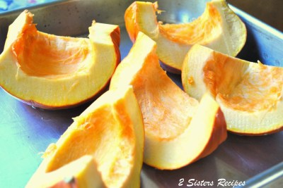 Small pumpkin is sliced into quarters and placed into a roasting pan. by 2sistersrecipes.com