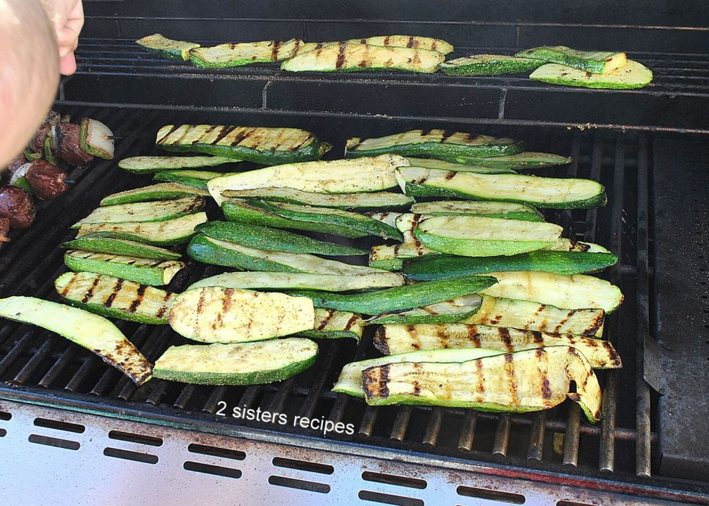 Zucchini is grilled on the barbecue by 2sistersrecipes.com