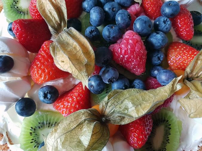 Birthday cake with blueberries, raspberries, strawberries, kiwi and physalis