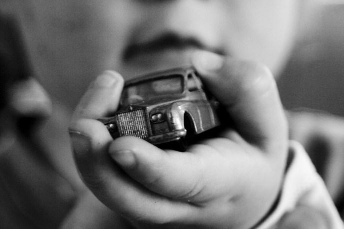 child holding toy car