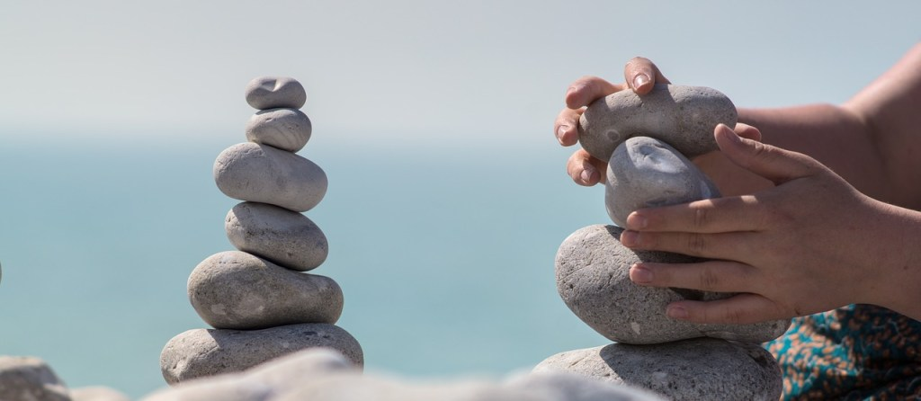 balanced tower of rocks with hands making another tower