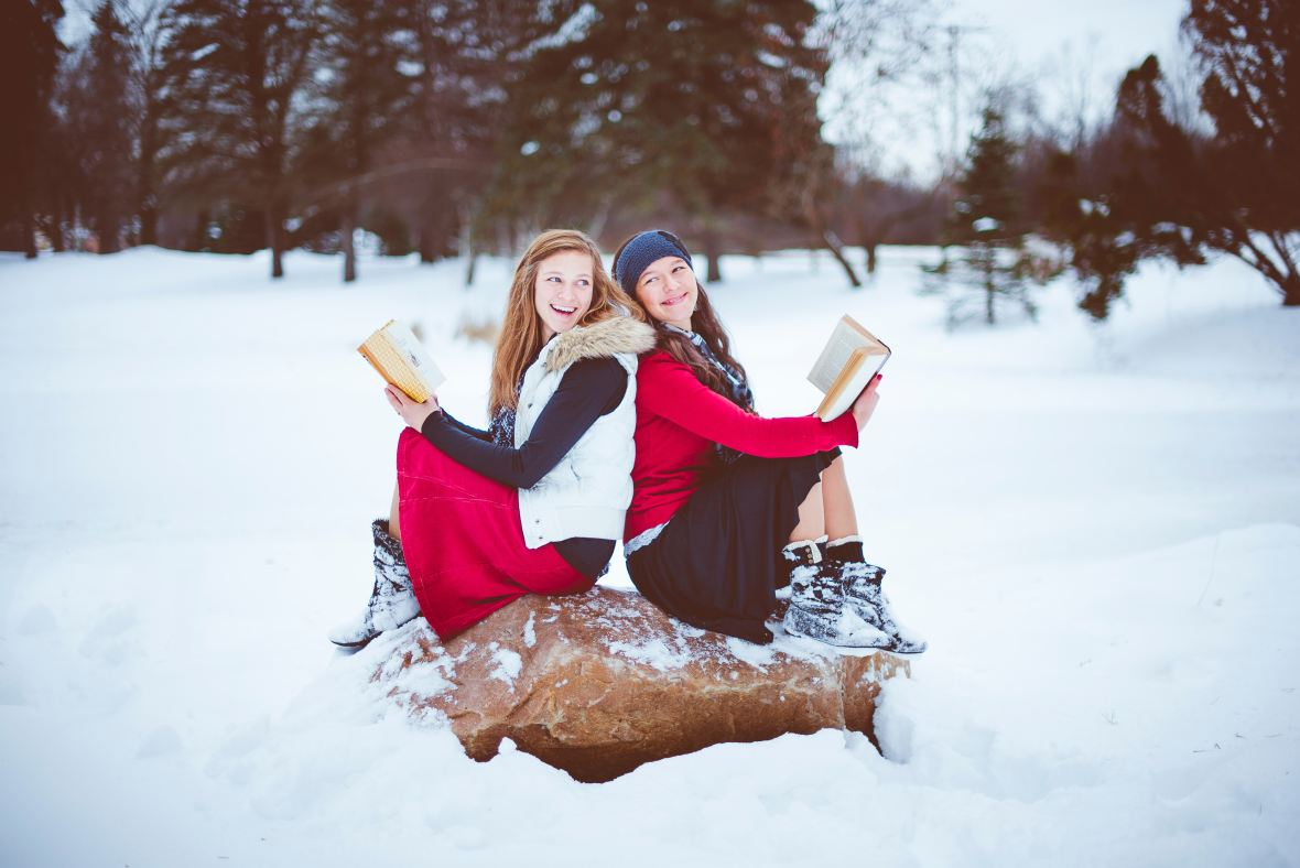 two smiling women in red sitting in snow with books