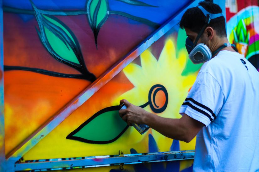 colourful photo of graffiti artist by Maxime Bhm via Unsplash