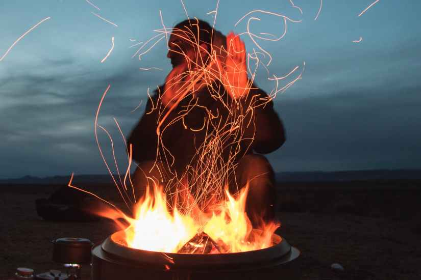 man sitting behind a fire pit, blue background representing burnout