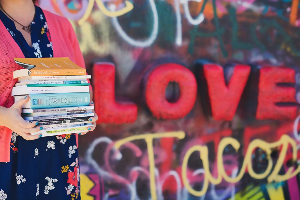 woman holding a pile of book in front of red letters spelling the word LOVE