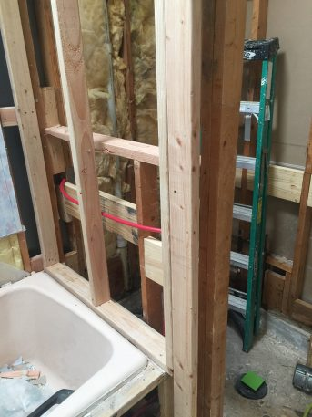 During - Moved wall towards tub to make room for large storage ledge in shower