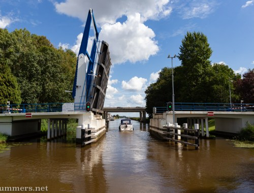 Boat going under a bridge in a Netherlands canal
