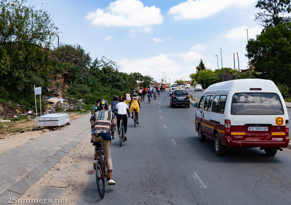 Cyclists riding up a hill in Alexandra Township.
