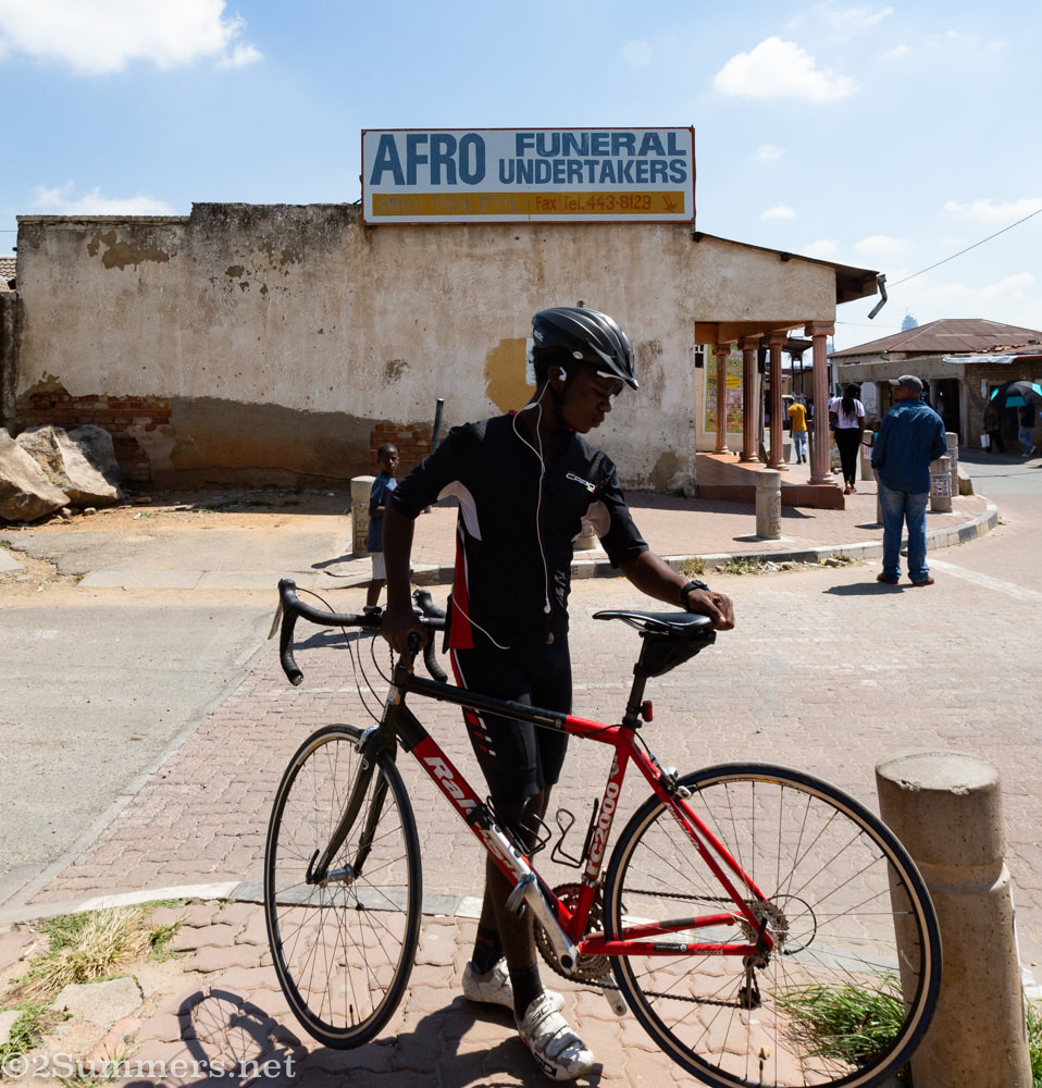 Cyclist in front of a funeral home in Alexandra Township