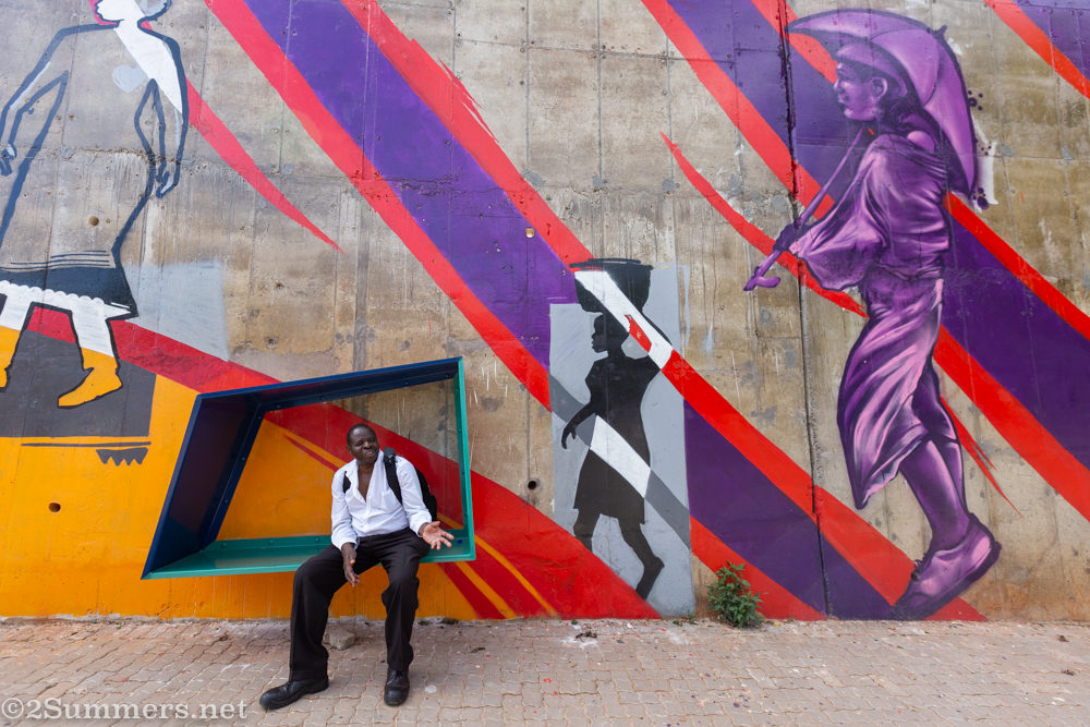 Man sits on a bench at the Louis Botha S-bend mural