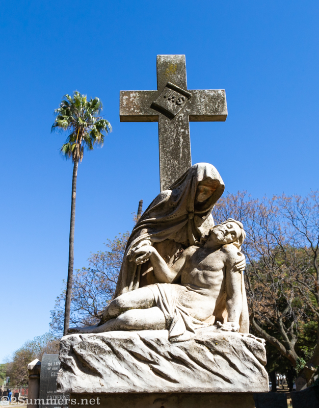Cemetery headstone and palm tree