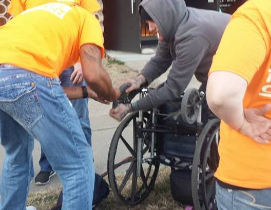 Making repairs to a homeless person's wheelchair.