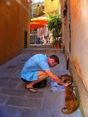 Chris Taylor petting cats in Cinque Terre Italy