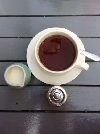 kop thee met melkkannetje en jam