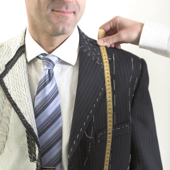 man getting measured for bespoke suit