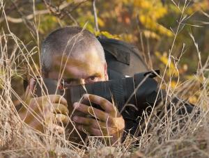 Mężczyzna obserwuje z ukrycia