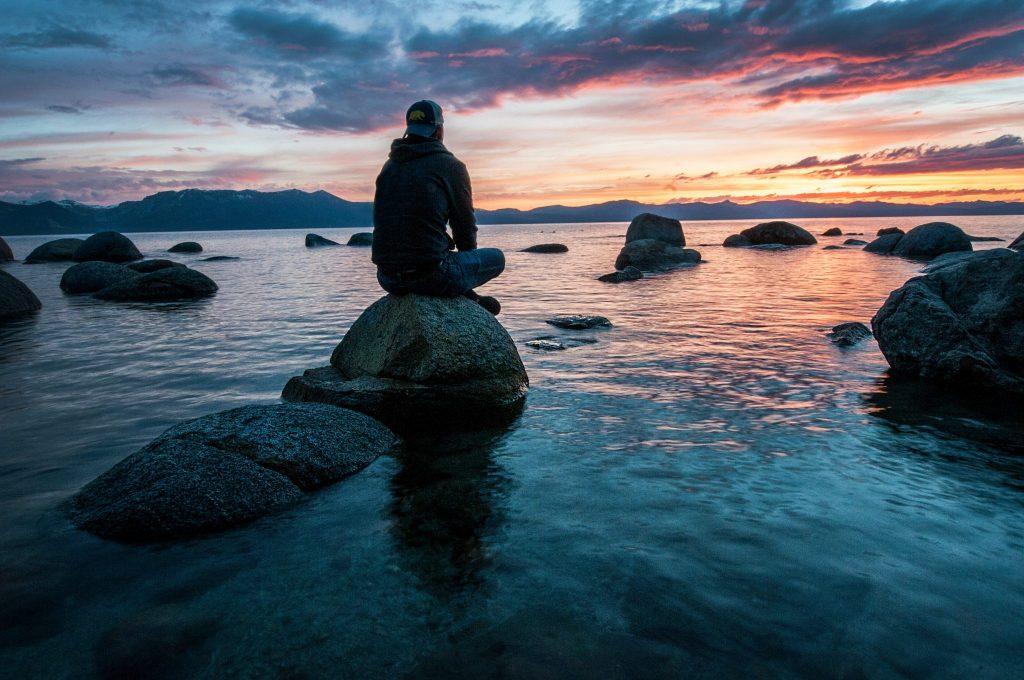 photo d'un homme méditant sur un rocher