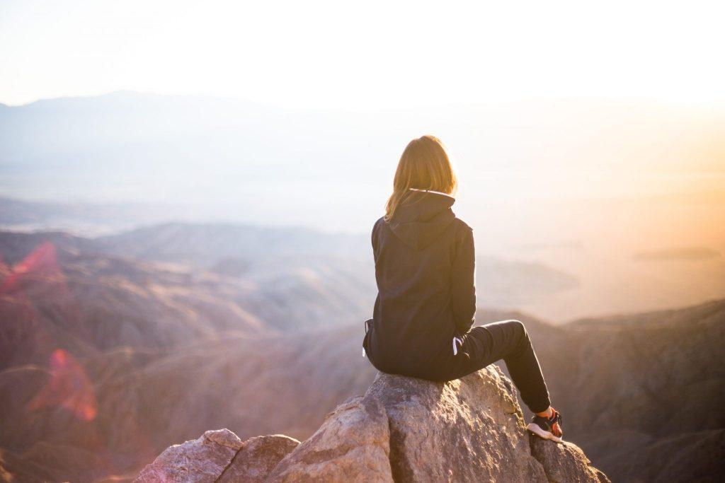 femme sur un rocher face à la montagne