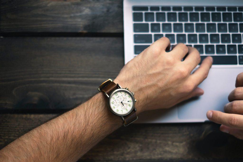 homme regardant l'heure sur sa montre pour gérer son temps