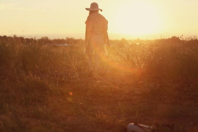 Femme dans un champ pendant un coucher de soleil qui profite de son temps libre
