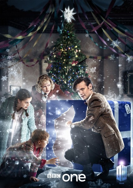 BBC promo - The Doctor is opening a big blue gift package in front of a festive tree, Mrs Arwell and her children look on