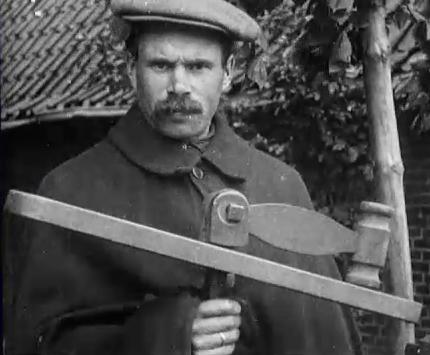 Klepperman met zijn klep, Amerongen, rond 1920. Foto uit filmfragment van het Nederlands Instituut voor Beeld en Geluid.