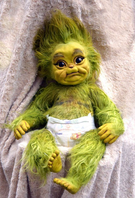 Baby Grinch lying on a blanket